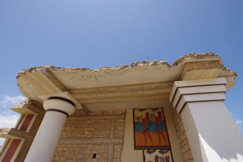 Ruine mit Säule und abgebrochener Decke vor blauem Himmel. An der Wand ein Gemälde mit zwei Frauen