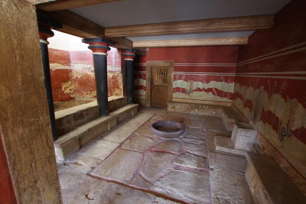 Raum mit Waschbecken und Thron. An der Wand rote Malereien.