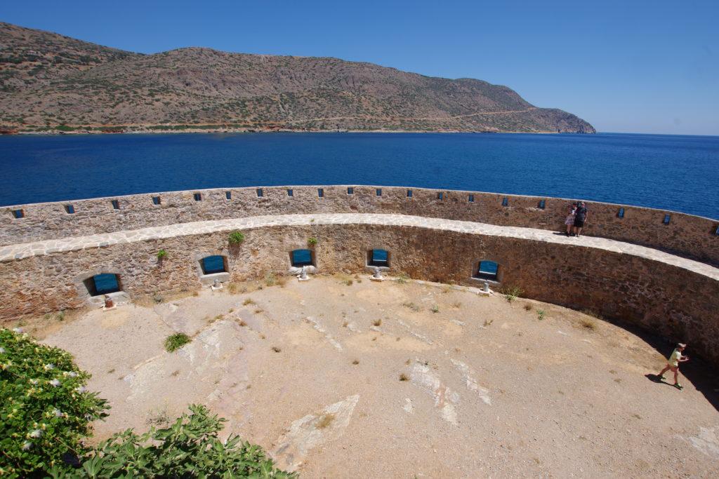 rundliche Festung mit Kanonenlöchern, dahinter tiefblaues Meer mit kargem Küstenstreifen