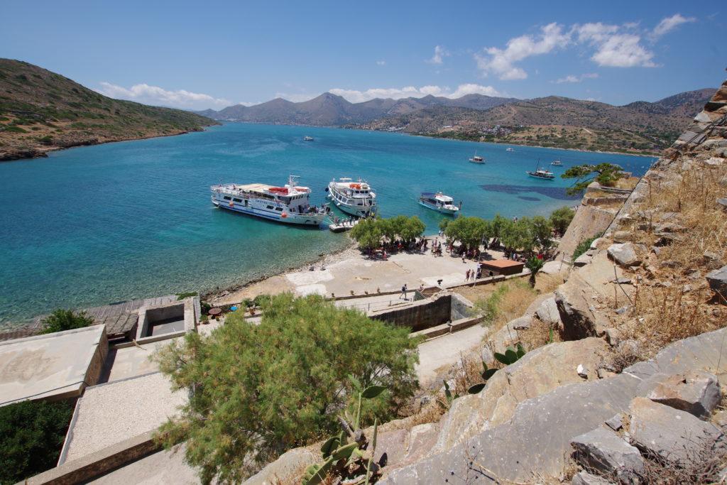 Blick auf traumhafte Küstenszenerie, Boote legen unterhalb einer Festung an, Touristen warten im Schatten der Bäume