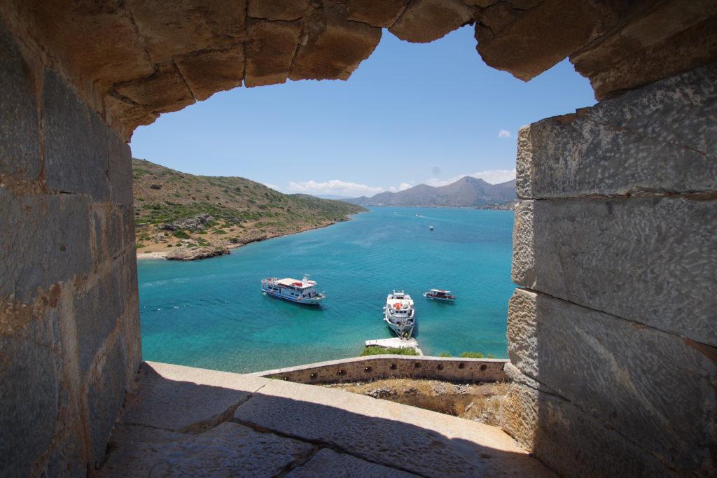 Blick aus einer Kanonenöffnung auf einen Küstenstreifen mit Booten und türkis blauem Meer bei strahlendem Sonnenschein