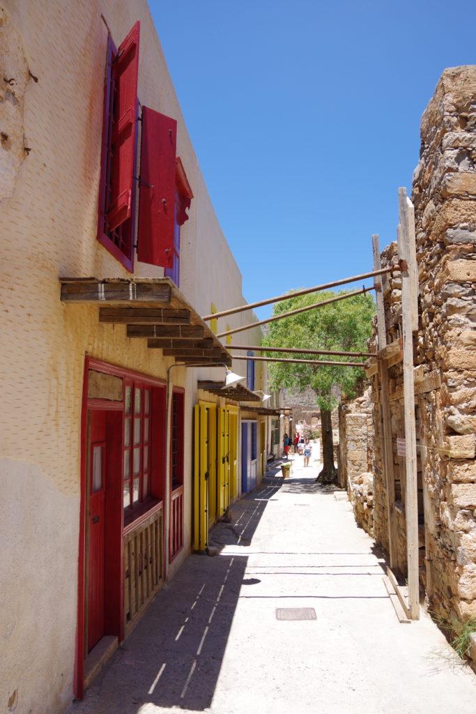 Gasse mit allein stehenden Baum bei sonnigem Wetter. Bunt bemalte Fenster und Türen an der linken Häuserreihe