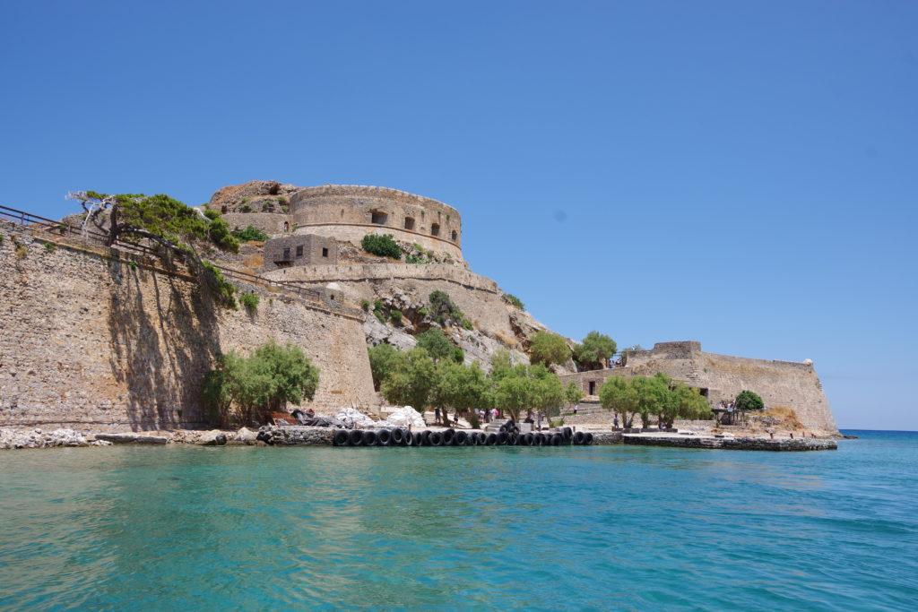 Im Vordergund türkisblaues Meer, im Hintergrund Bootsanlegestelle unter einer Festung bei blauem Himmel