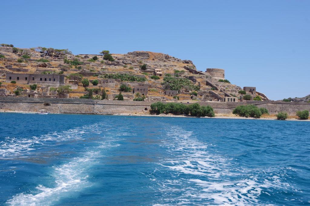 Im Vordergrund Meer mit Bootsspur. im Hintergrund kleine Insel mit Festung und verlassenen Häusern bebaut