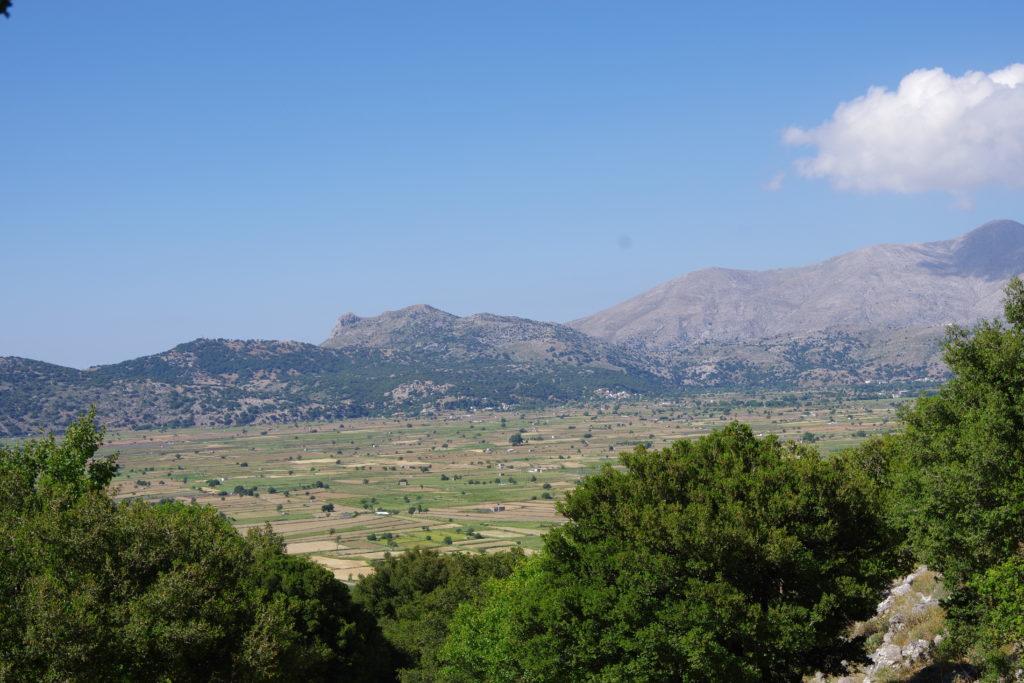 Blick auf Kesseltal umrahmt von Bergen bei blauem Himmel. Unten im Bild Baumkronen