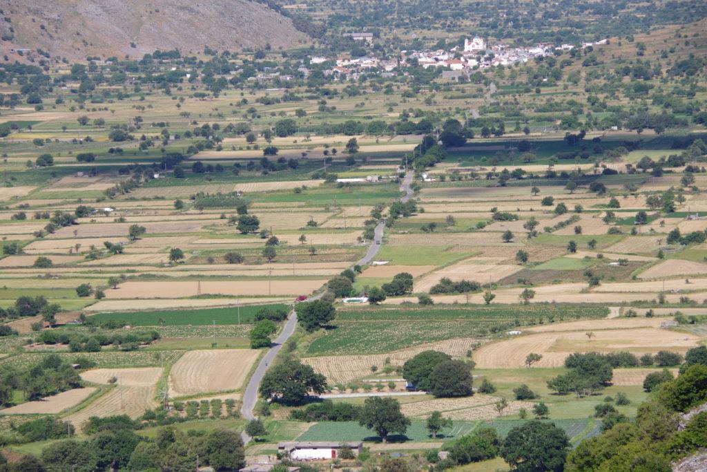 Blick von oben auf Ebene mit Feldern, durch deren Mitte eine Straße zu einem Dorf führt