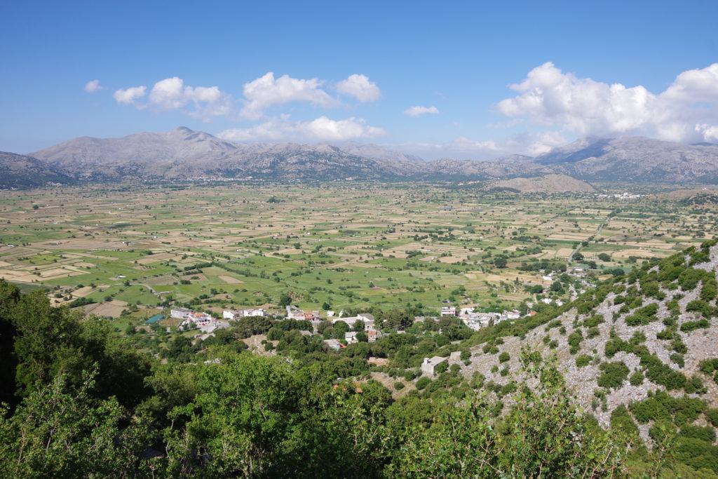 Blick von oben auf flache Hochebene, umrahmt von Bergen, bei schönem Wetter