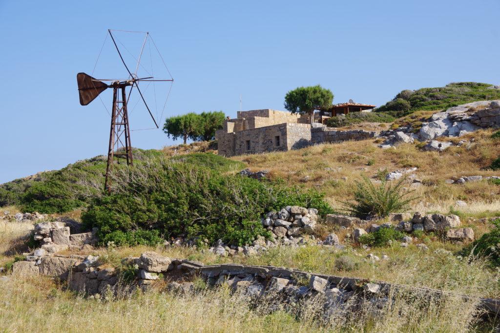 rostiges Windrad vor Hügel mit einfachen Steinbauten