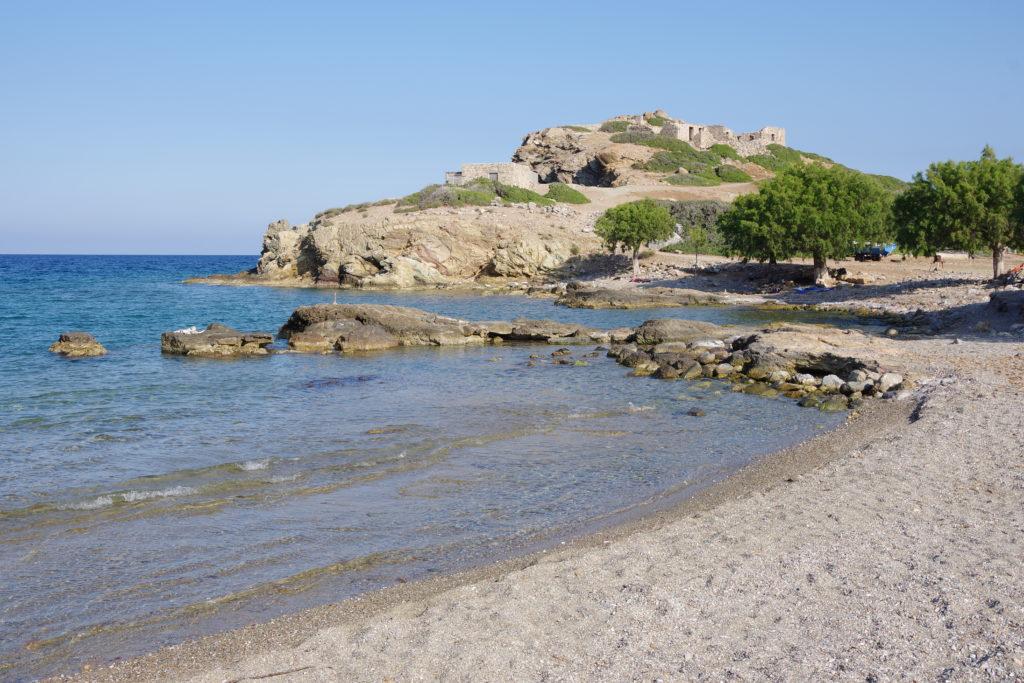 naturbelassener Strand mit Meer, dahinter auf Hügel Ruinen
