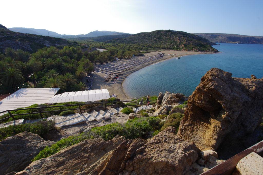 Blick von oben auf Strand mit Liegstühlen, dahinter Wald aus Dattelpalmen
