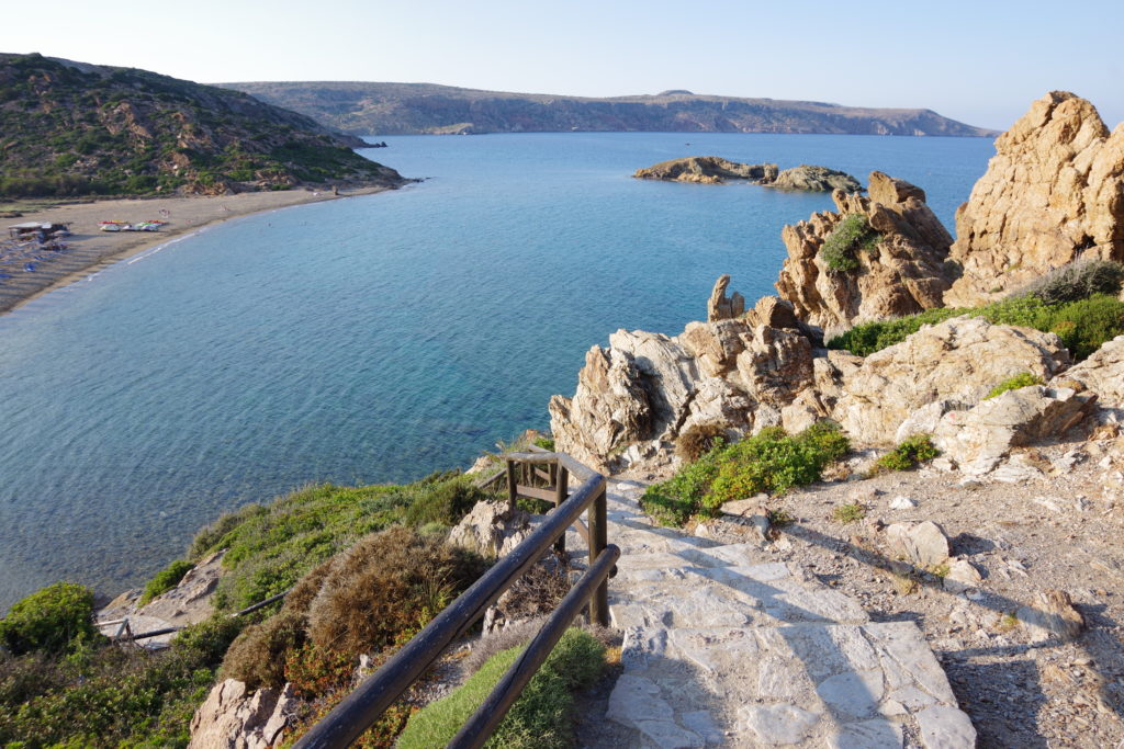 Streppenstufen mit Geländer auf Steilküste, dahinter Strand und Bucht und kleiner Insel