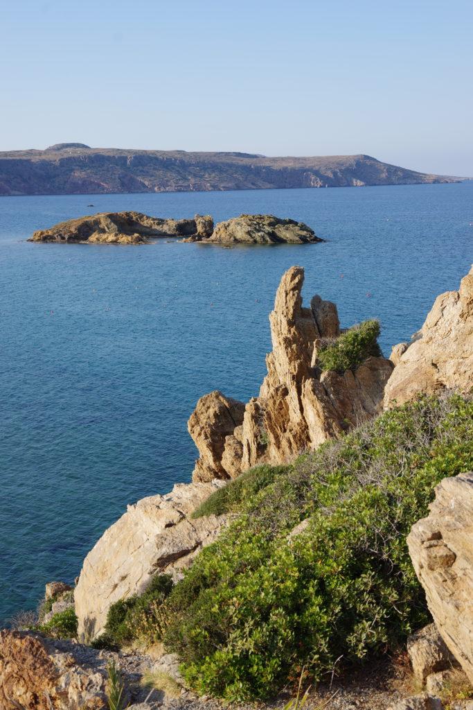 schroffe Felsformation an Steilküste, Bucht mit kleiner Insel