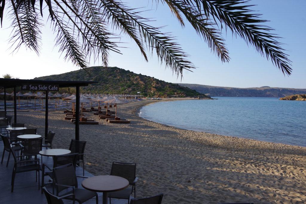 Strand mit Liegestühlen und Sonnenschirmen. Im Vordergrund Terrasse eines Cafes und Blätter einer Palme