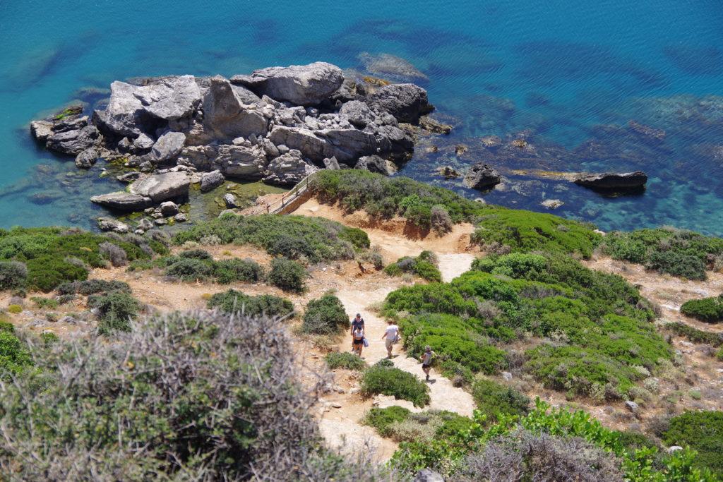 Wanderweg an Steilküste, dahinter tiefblaues Meer mit Ansammlung von großen Felsbrocken