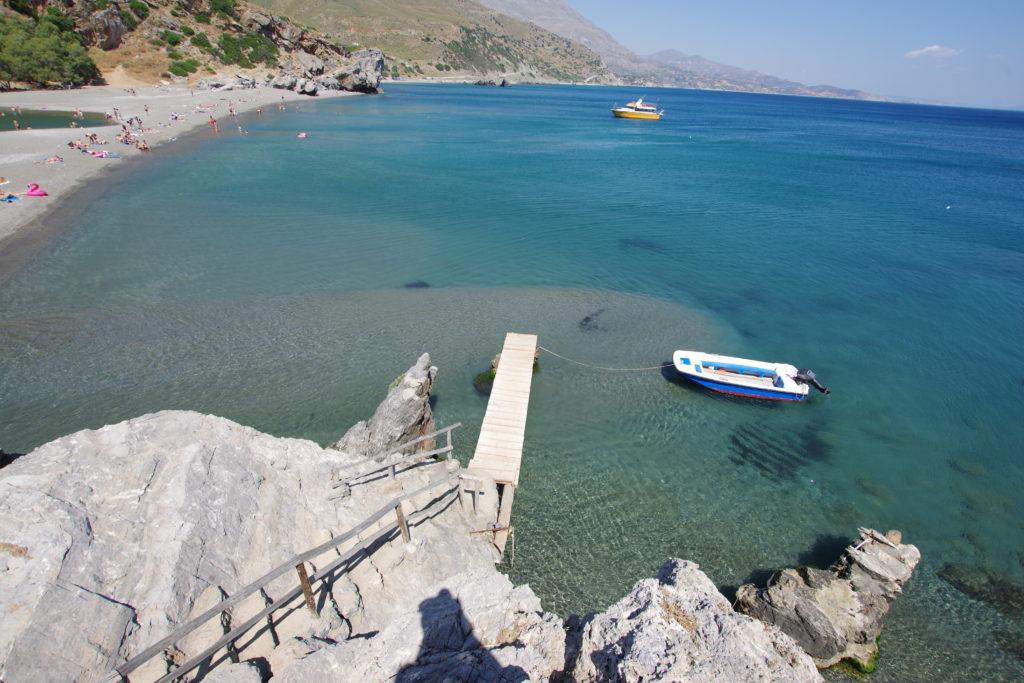 Blick von oben auf Badestrand und Bootsanlegestelle mit klarem Meerwasser.