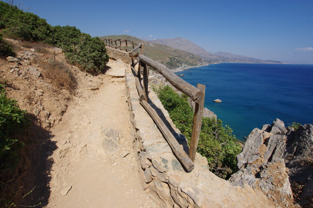 Weg mit Geländer an Steilküste über tiefblauem Meer.