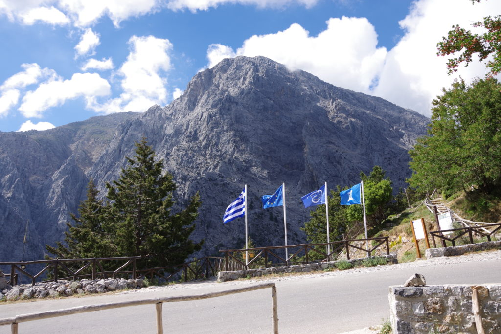 Gebirgsmassiv hinter Parkfläche mit blauen Flaggen