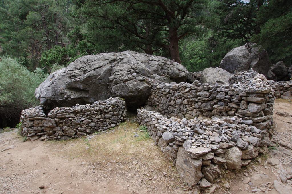 Unterschlupf unter großem Felsen und davor auf geschlichteten Steinen