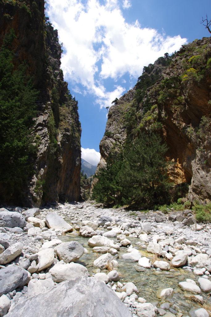 Canyonartiger Einschnitt mit Gebirgsbach bei schönem Wetter