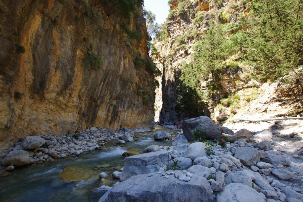 Gebirgsbach zwischen Geröll in Schlucht mit senkrechten Felswänden