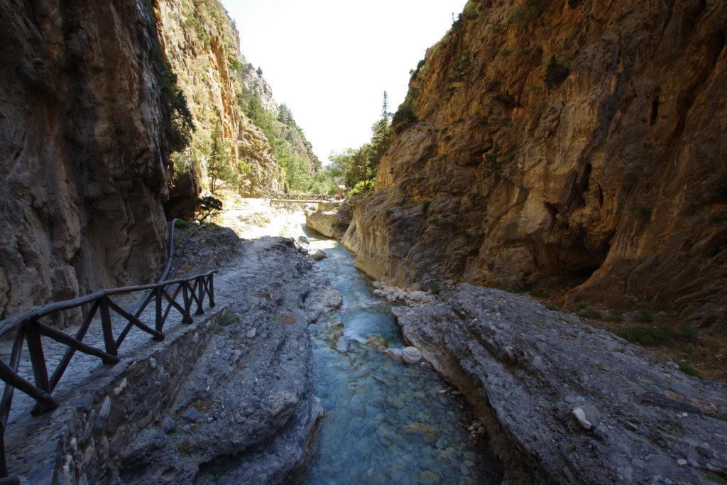 Gebirgsbach zwischen Felswänden, links ein gemauerter Weg mit Holzgeländer