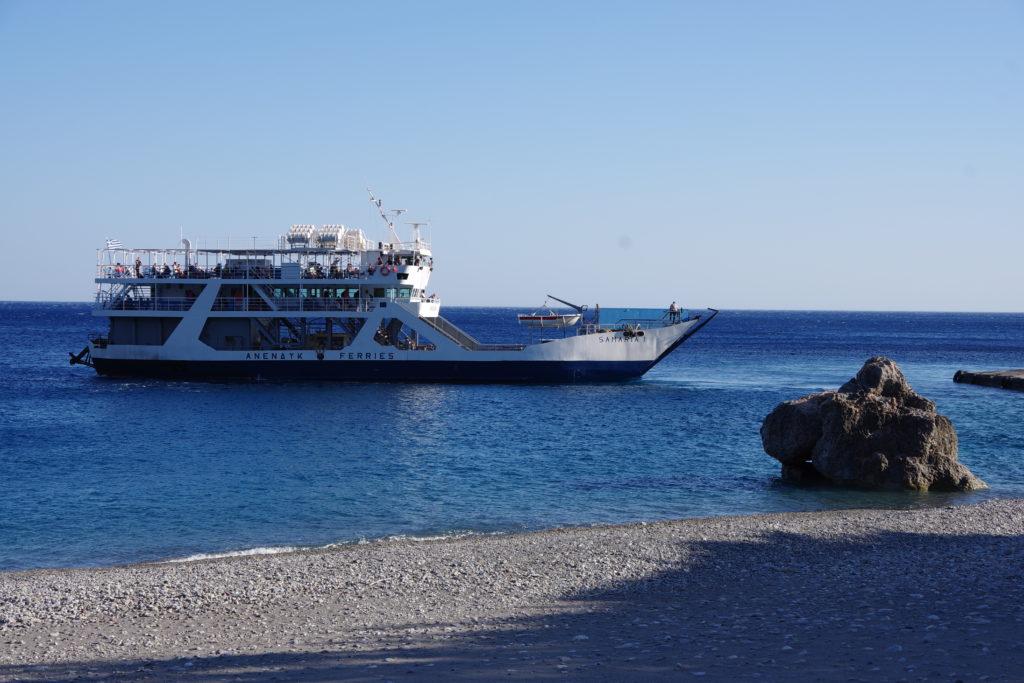 Fähre mit Passagieren an Kiessstrand mit tiefblauem Meer
