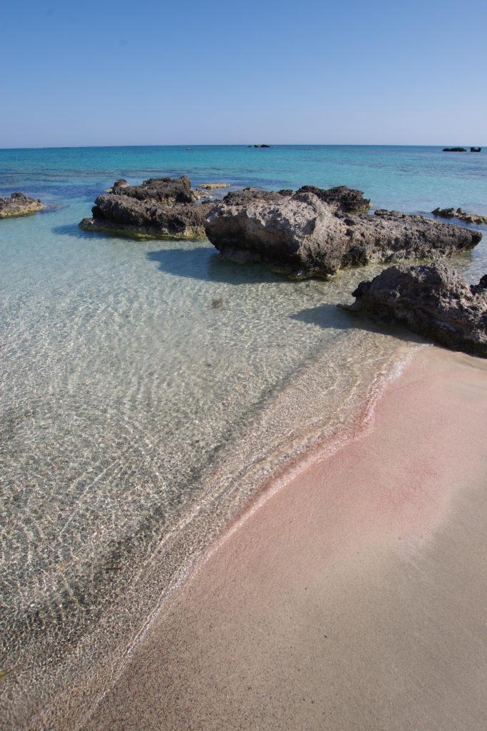 Seichter Strand mit Felsbrocken. Rosa gefärbter Sand am Wasser-Land-Übergang.