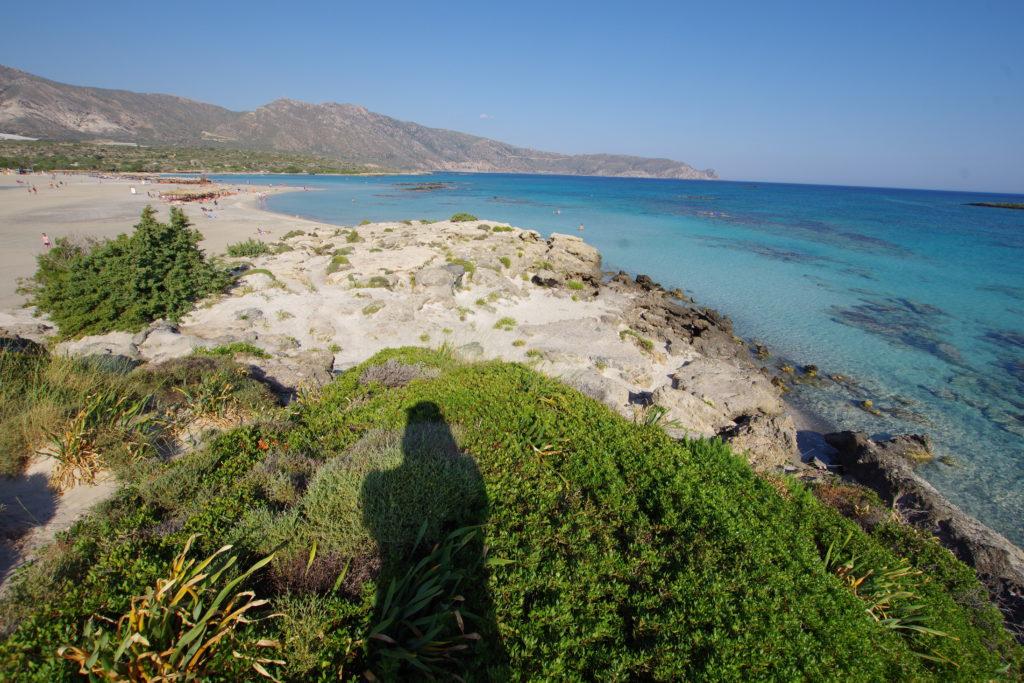 Blick auf Sandbank mit Sonnenschirme, Liegestühle und Touristen, daneben türkis-blaues Meer. Im Vordergrund Dünen mit grünen Sträuchern.