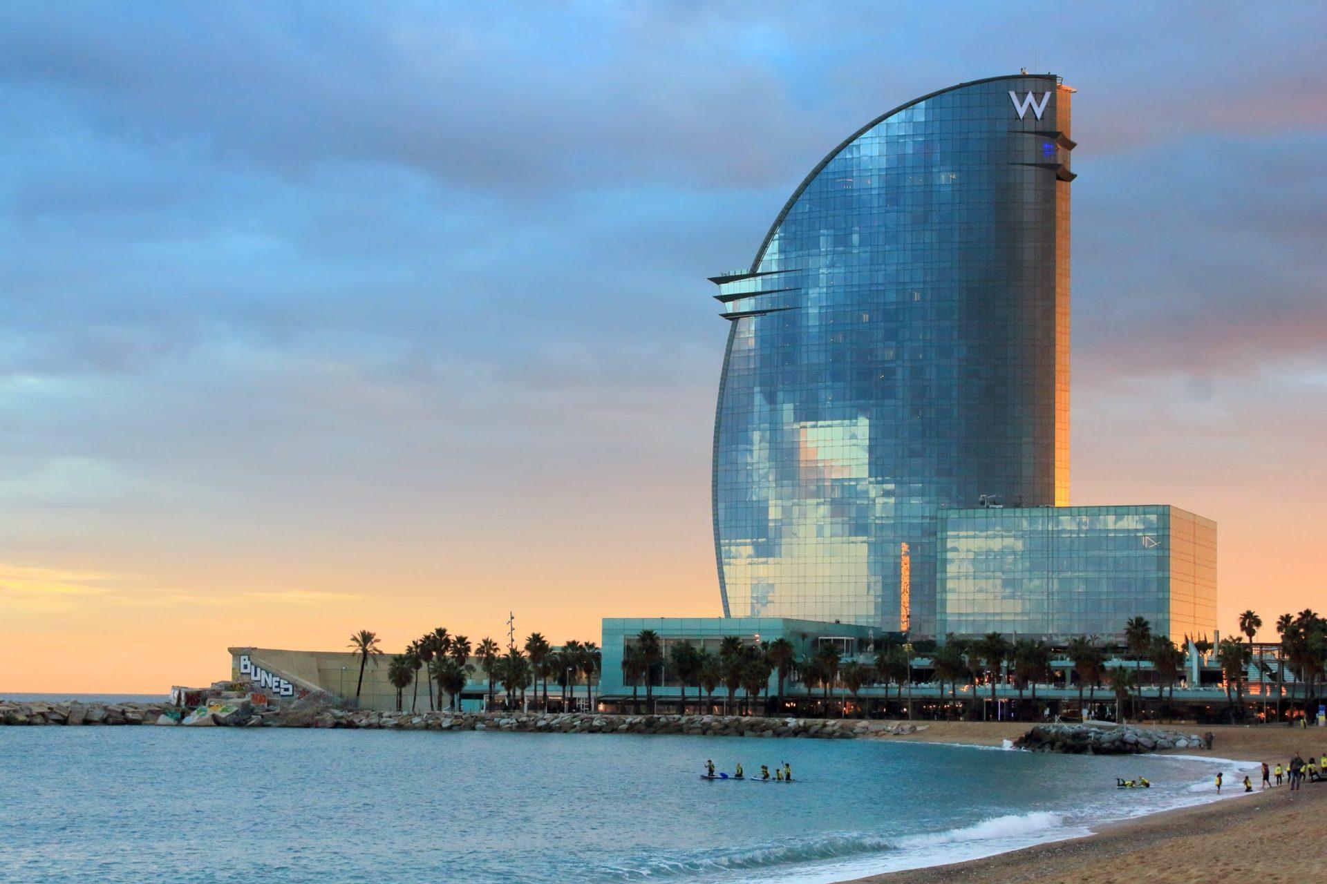 Wassertemperatur Barcelona: Hotel W mit Badestrand und Palmen bei Sonnenuntergang