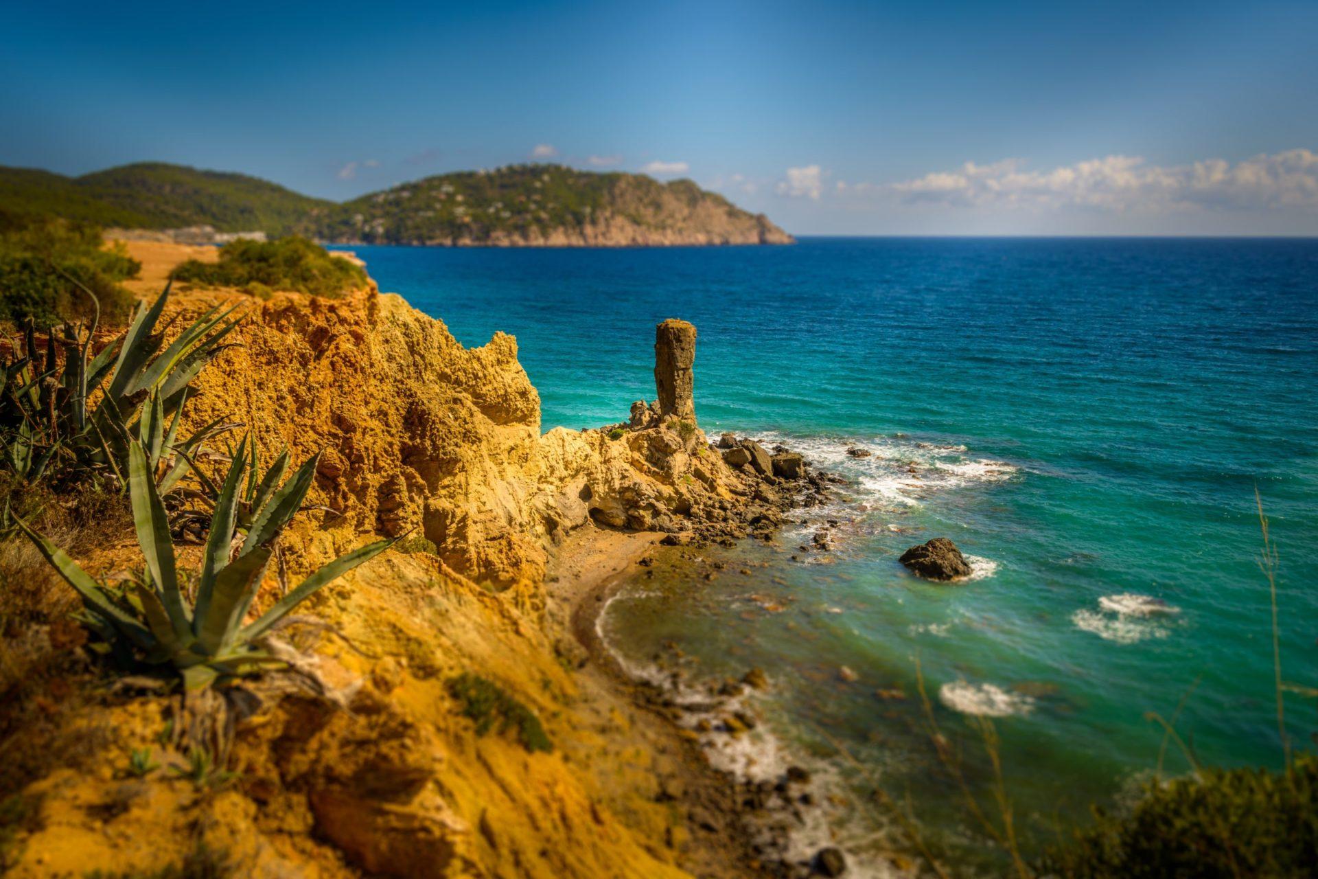 Wassertemperatur Ibiza: Isoliert stehende Felsnadel vor einer Steilküste mit türkis-blauem Mittelmeer