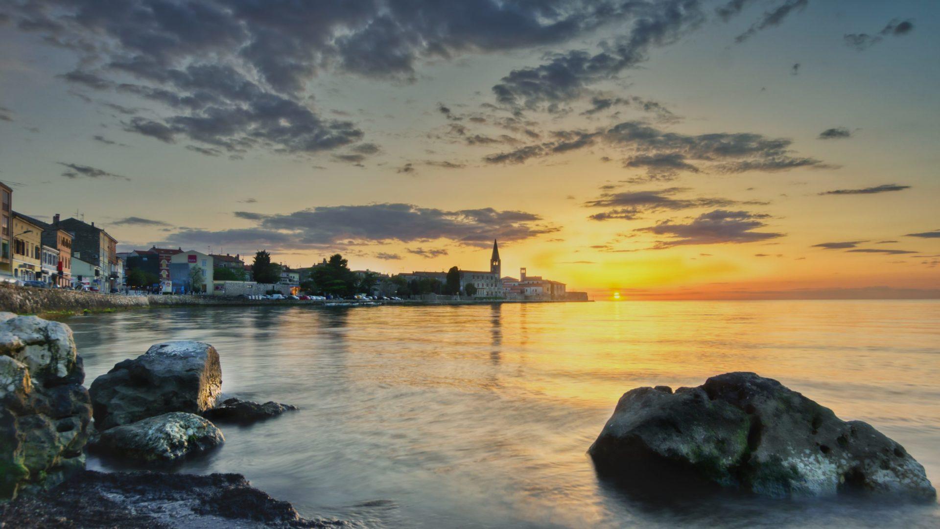 Wassertemperatur Porec: Blick über die Bucht von Porec auf die Altstadt mit Euphrasius-Basilika bei Sonnenuntergang