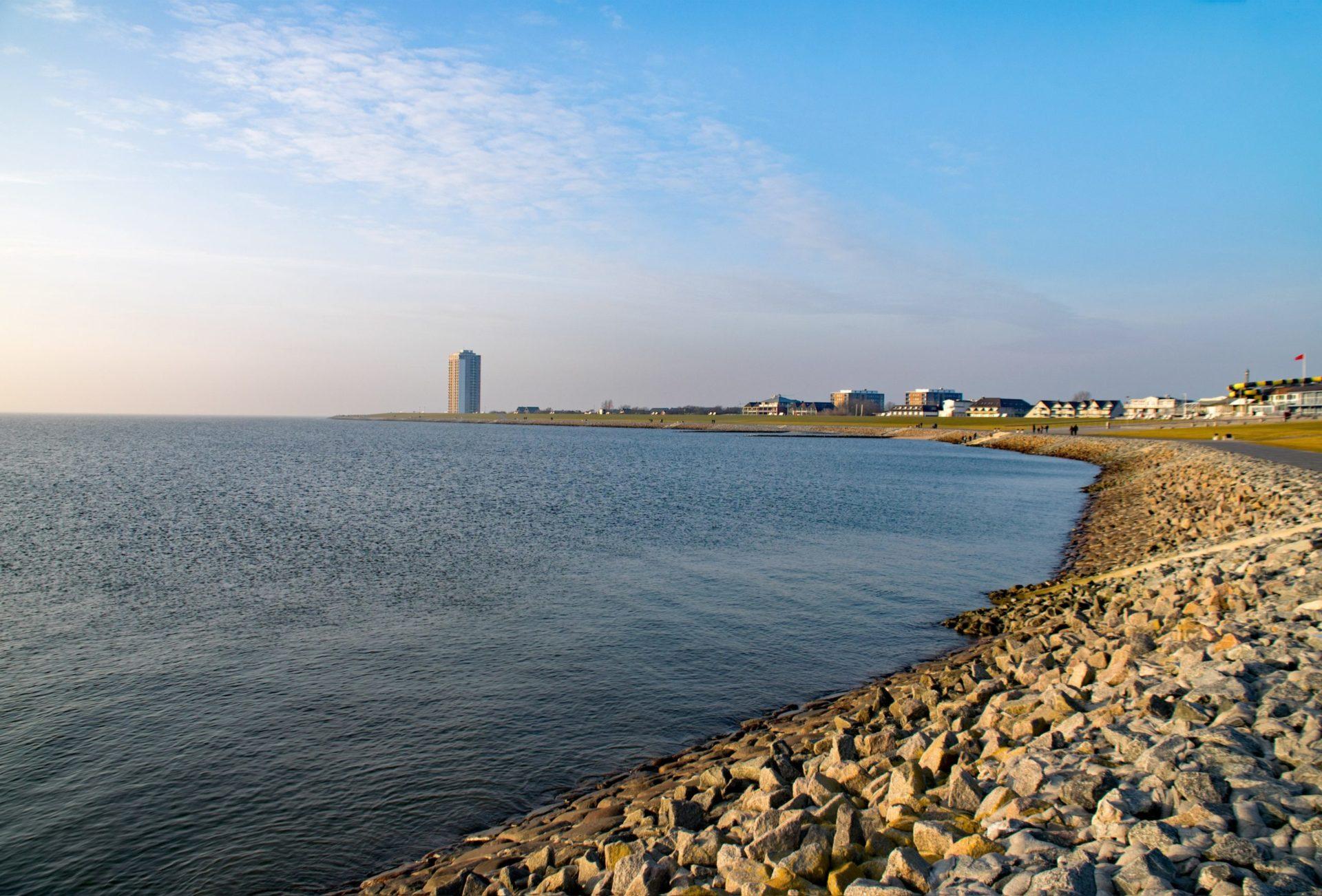 Wassertemperatur Büsum: Damm mit Nordsee und Hochhaus von Büsum am Horizont