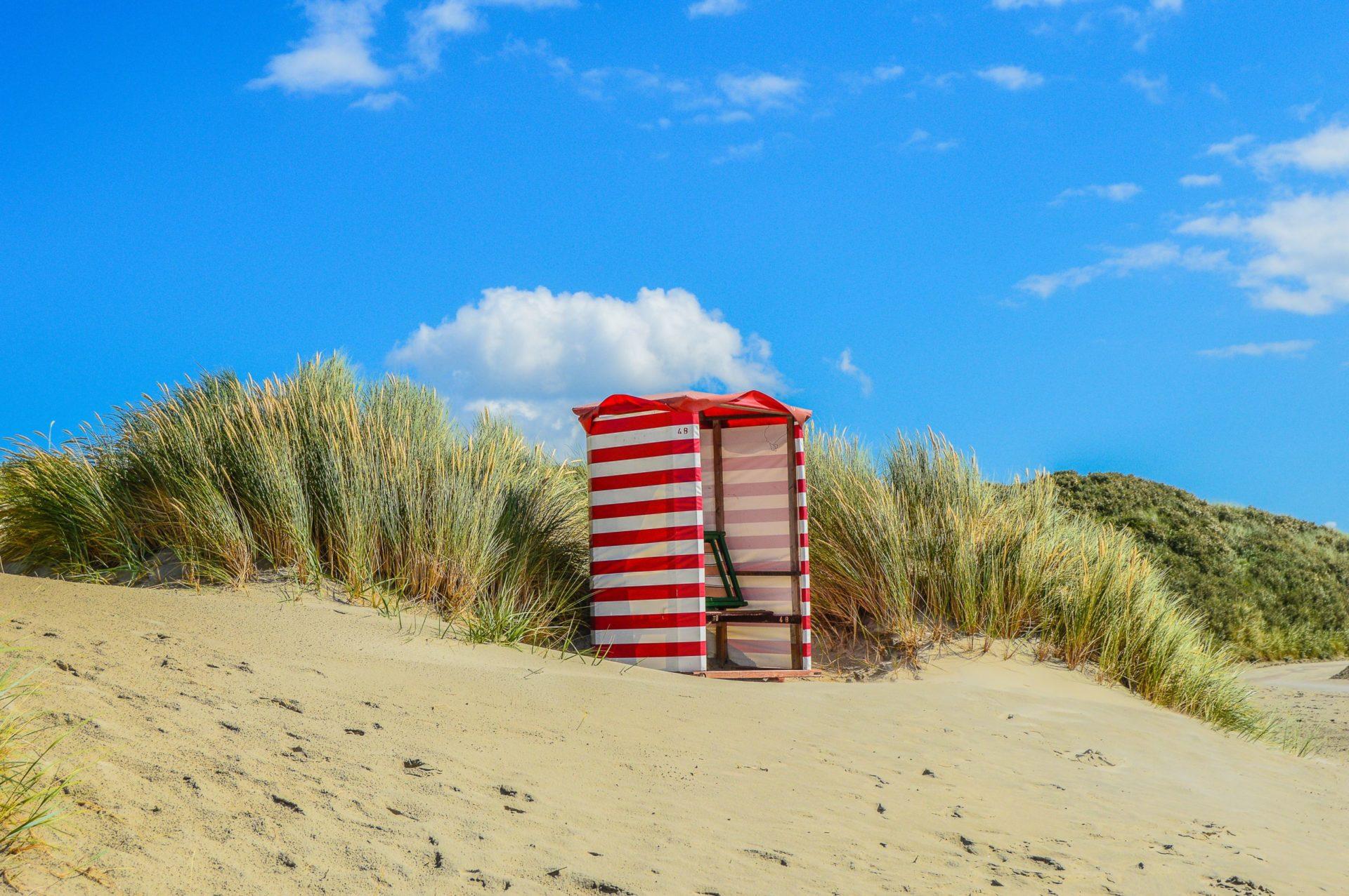 Wassertemperatur Borkum: Roter Strandkorb auf Sanddüne mit Gras unter blauem Himmel auf Borkum