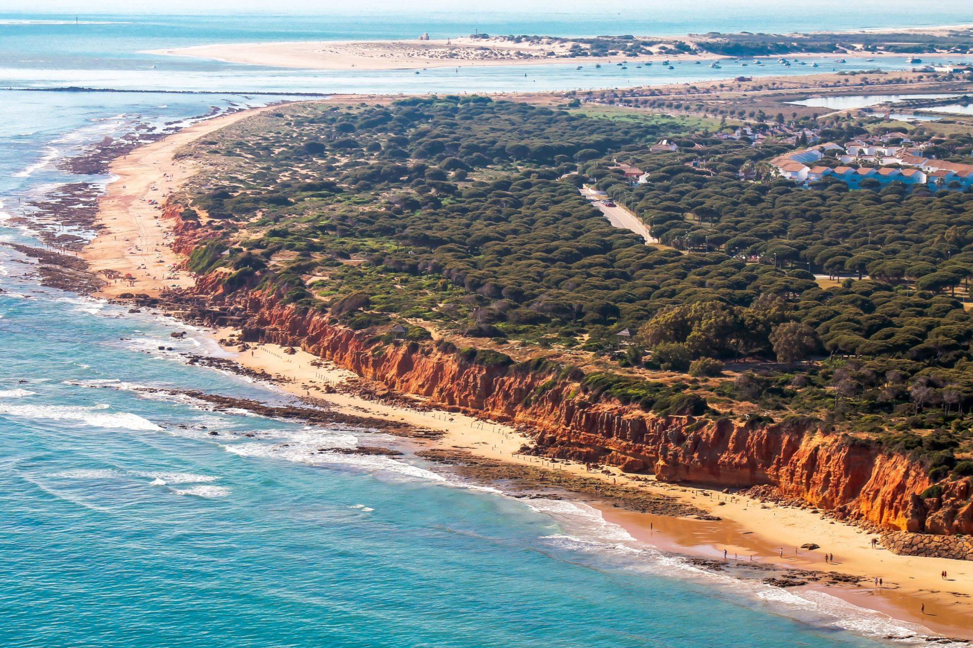 Wassertemperatur Cadiz: Strand mit rötlicher Steilküste Playa Santi Petri bei Chiclana de la Frontera an der Mündung des Caño de Sancti Petri aus der Luft