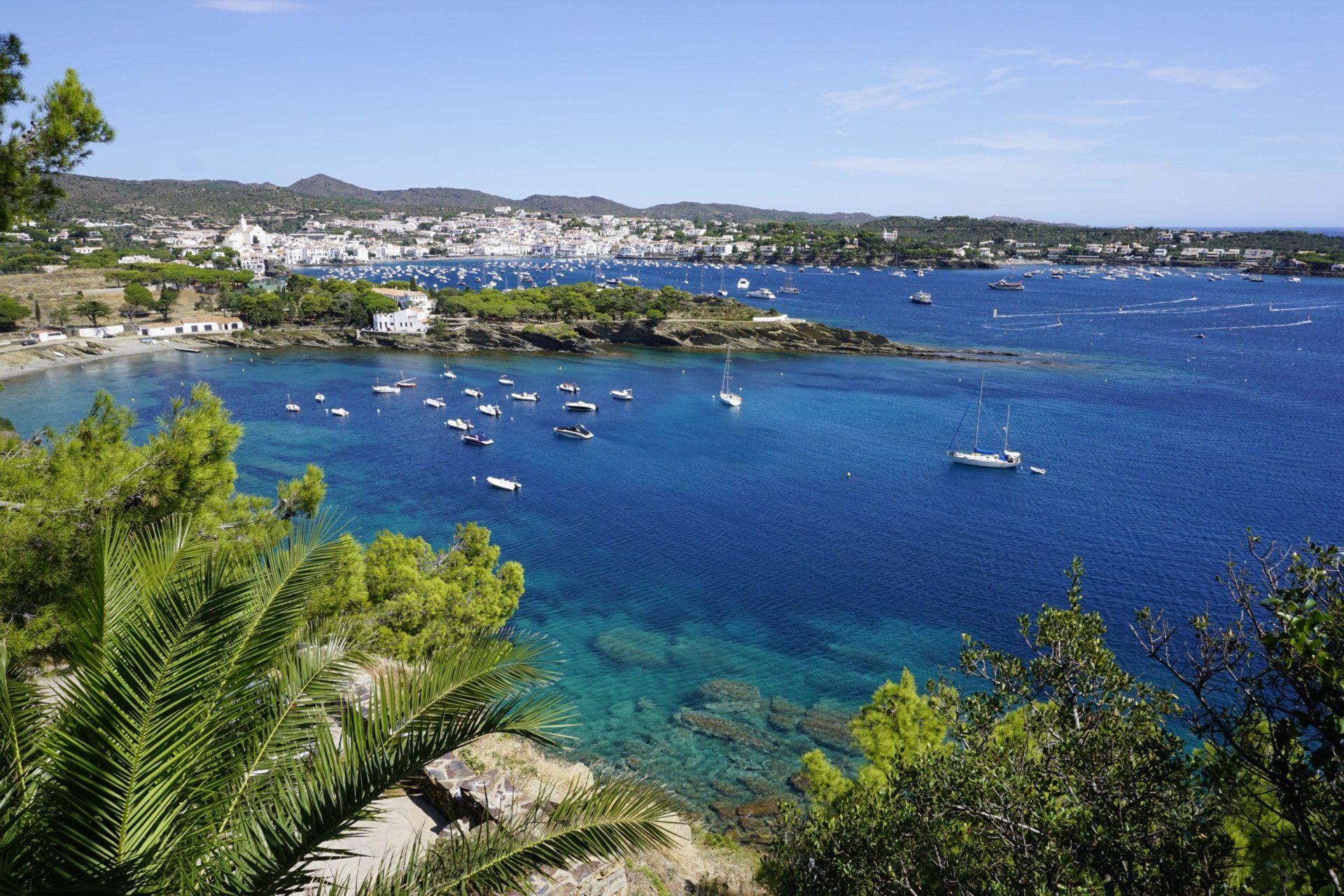 Wassertemperatur Costa Brava: Bucht des Fischerdorfes Cadaqués mit Kirche Santa Maria und Halbinsel Cap de Creus