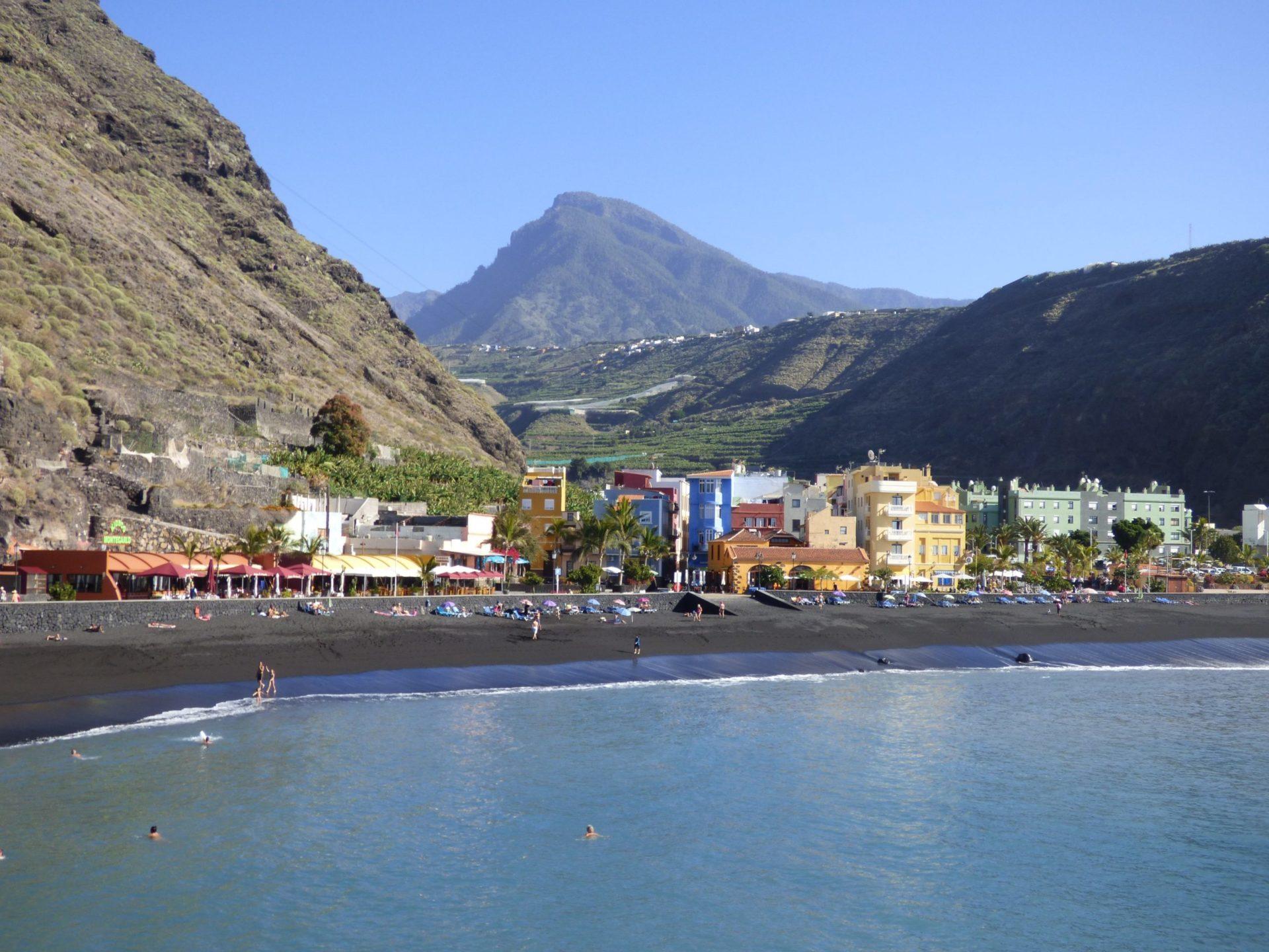 Wassertemperatur La Palma: Badestrand von Puerto de Tazacorte mit bunten Häusern, schwarzem Sand und gebirgigem Hinterland