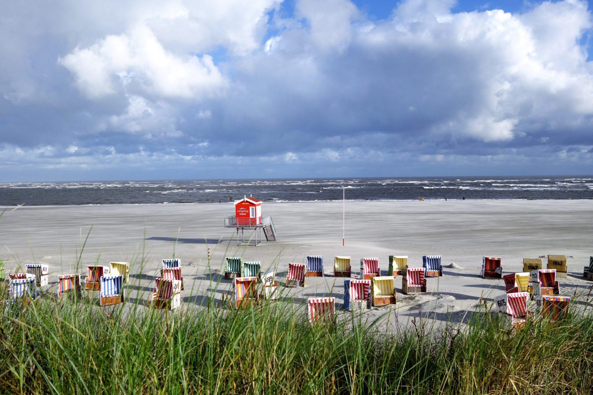 Wassertemperatur Langeoog: Blick über den bewachten Badestrand mit Strandkörben und Wachhäusschen beim Ort Langeoog, im Vordergrund Dünengras, im Hintergrund die Nordsee