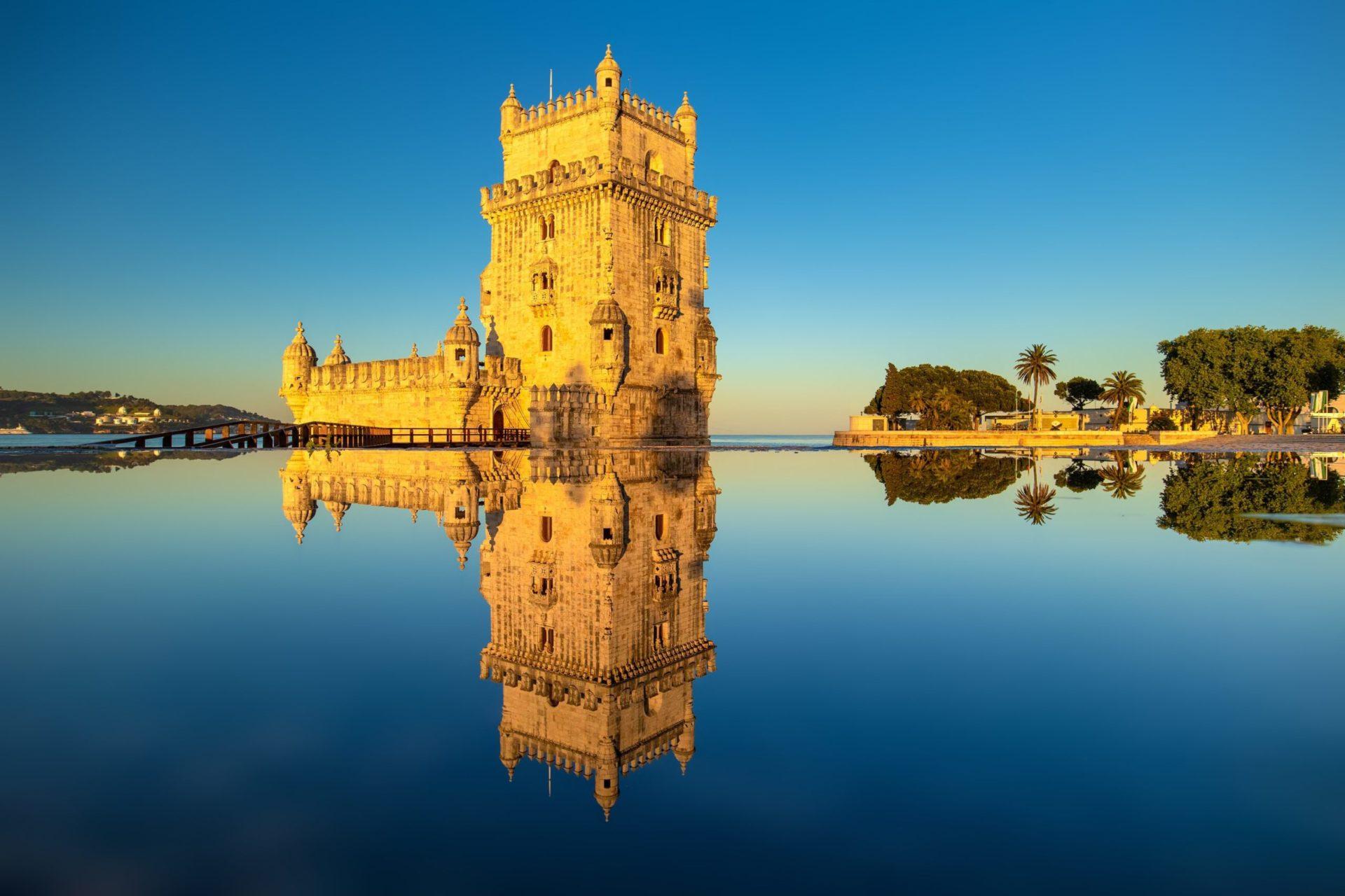 Wassertemperatur Lissabon: Torre de Belém spiegelt sich im stillen Wasser bei wolkenlosem Himmel.