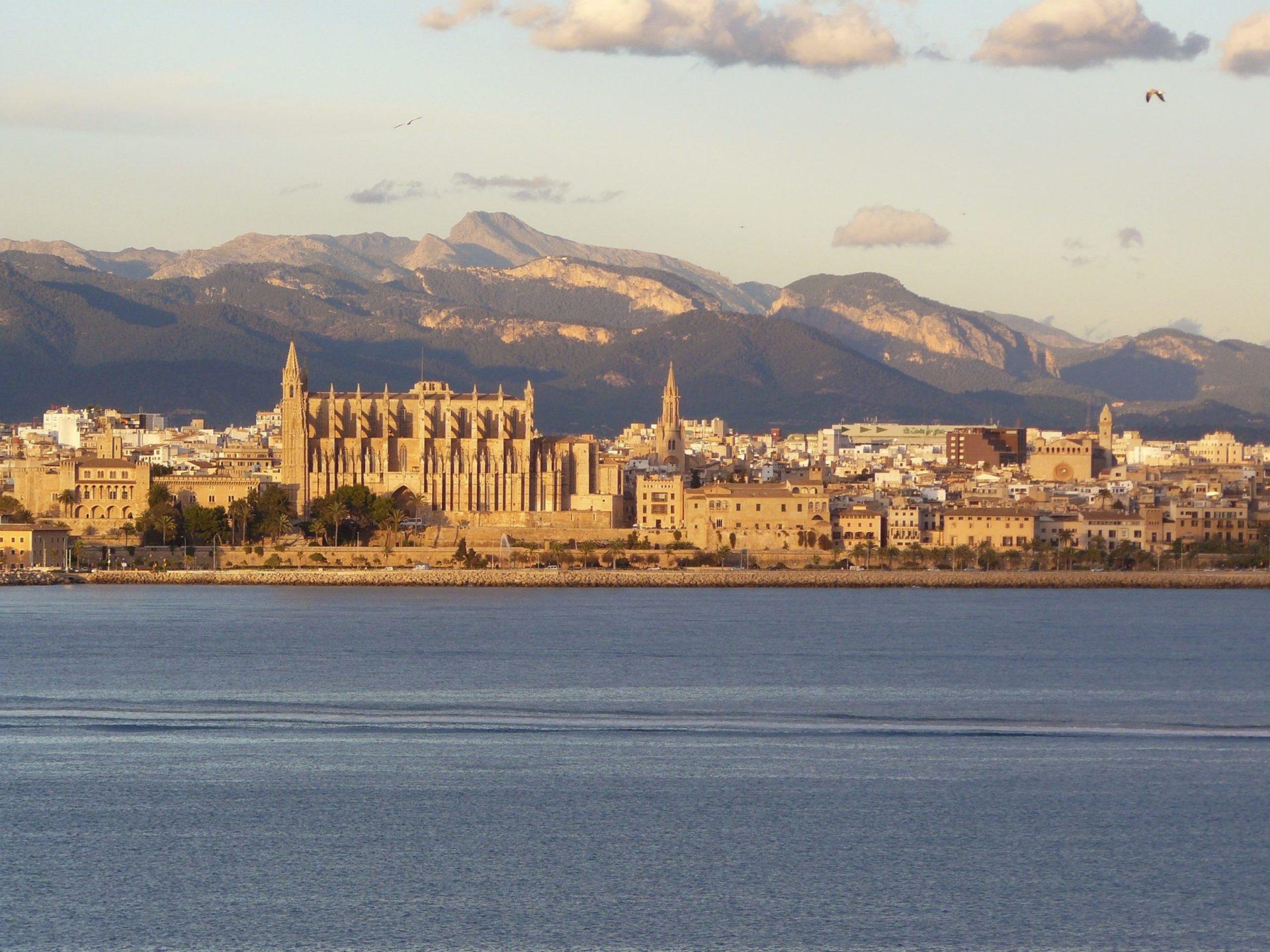 Wassertemperatur Palma de Mallorca: Blick vom Mittelmeer auf Palma de Mallorca, etwas links der Bildmitte die Kathedrale von Palma, in der Bildmitte der Kirchturm von Iglesia de Santa Eulàlia, im Hintergrund das Tramuntana-Gebirge