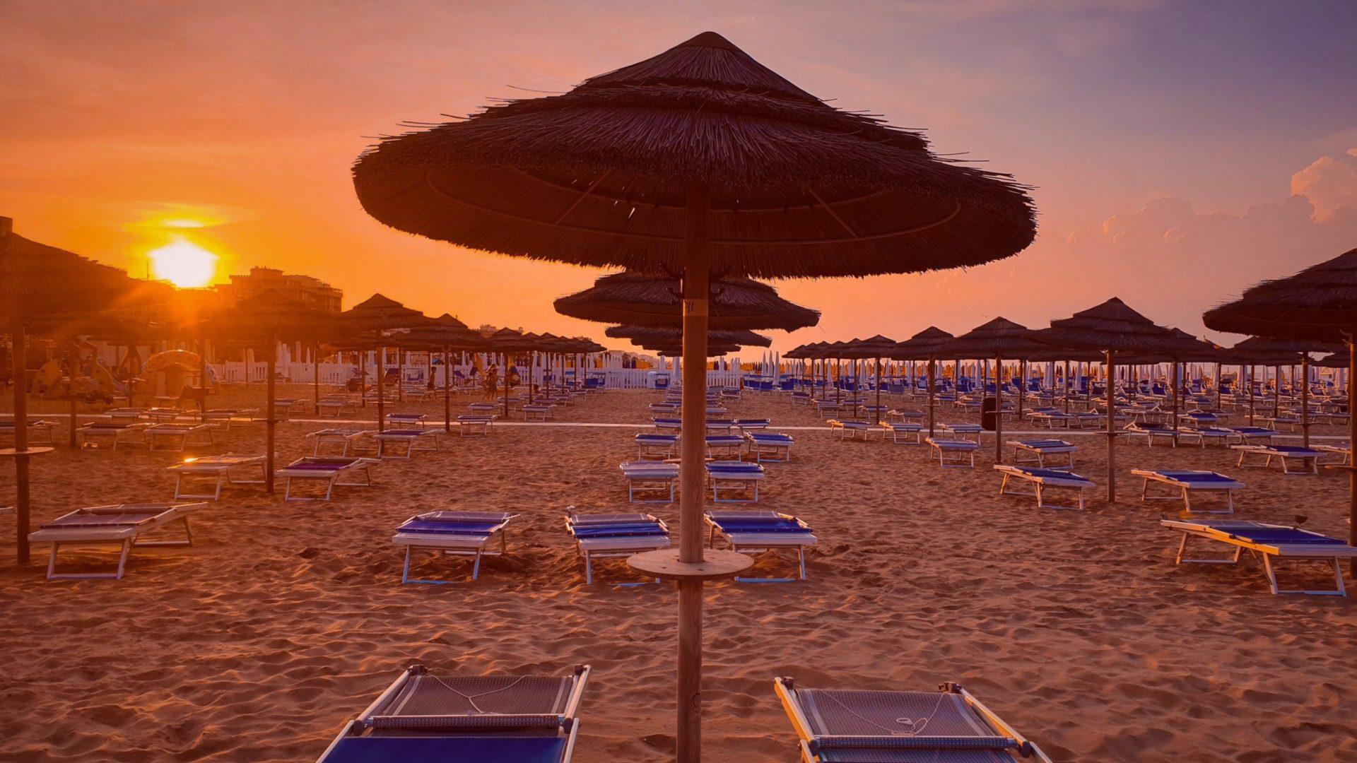 Wassertemperatur Rimini: Liegestühle und Sonnenschirme am Strand von Rimini bei Sonnenuntergang