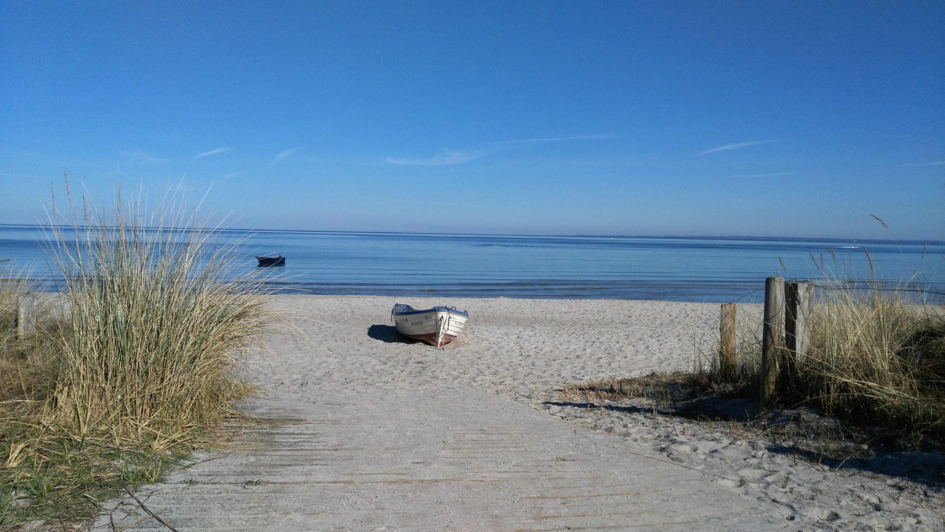 Wassertemperatur Scharbeutz: Sandstrand mit tiefblauem Meer, Dünengras und Boot