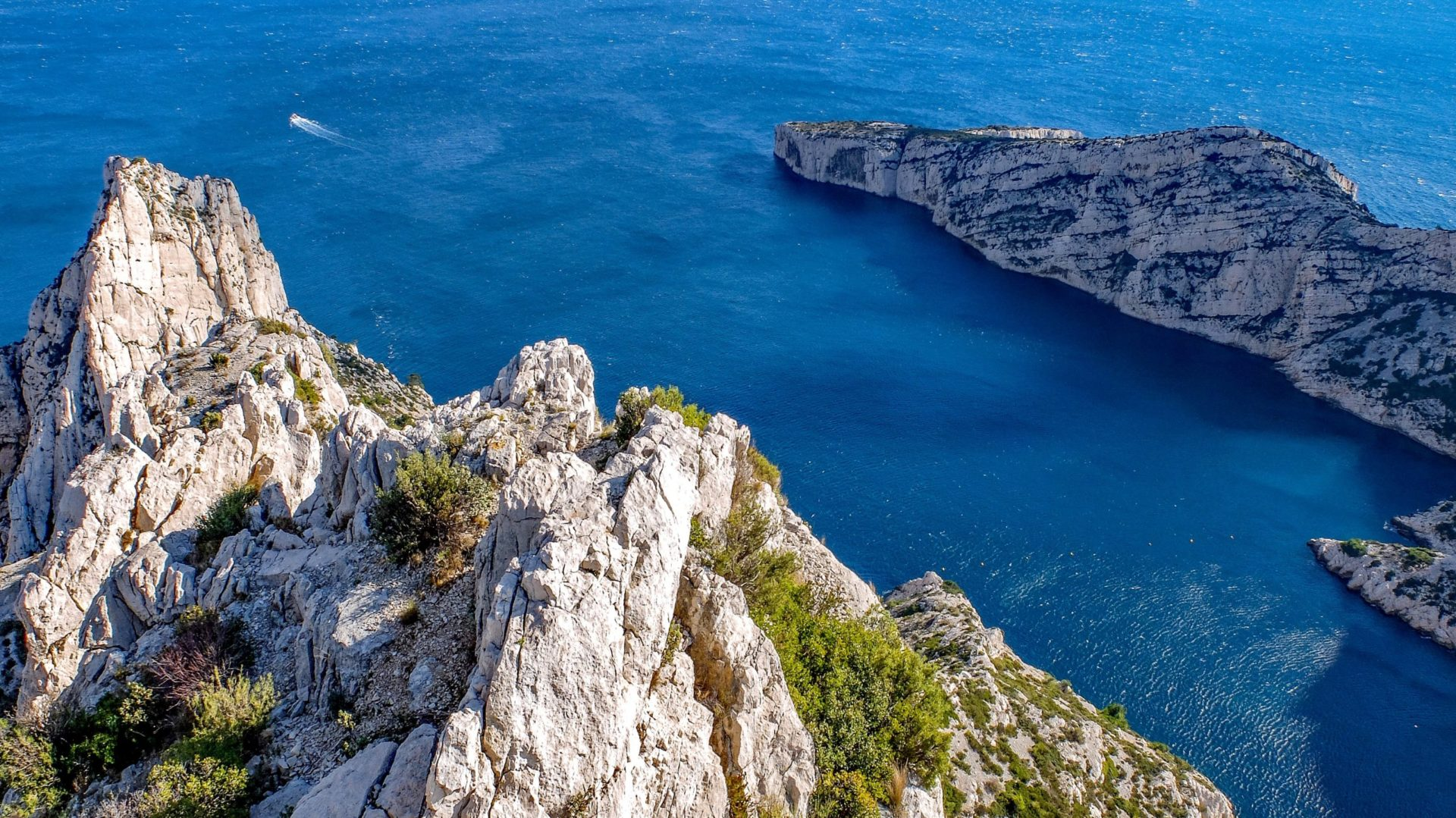 Wassertemperatur Marseille: Blick von den Kalksteinklippen des Massif des Calanques aufs dunkelblaue Mittelmeer der Felsbucht Calanque de Morgiou