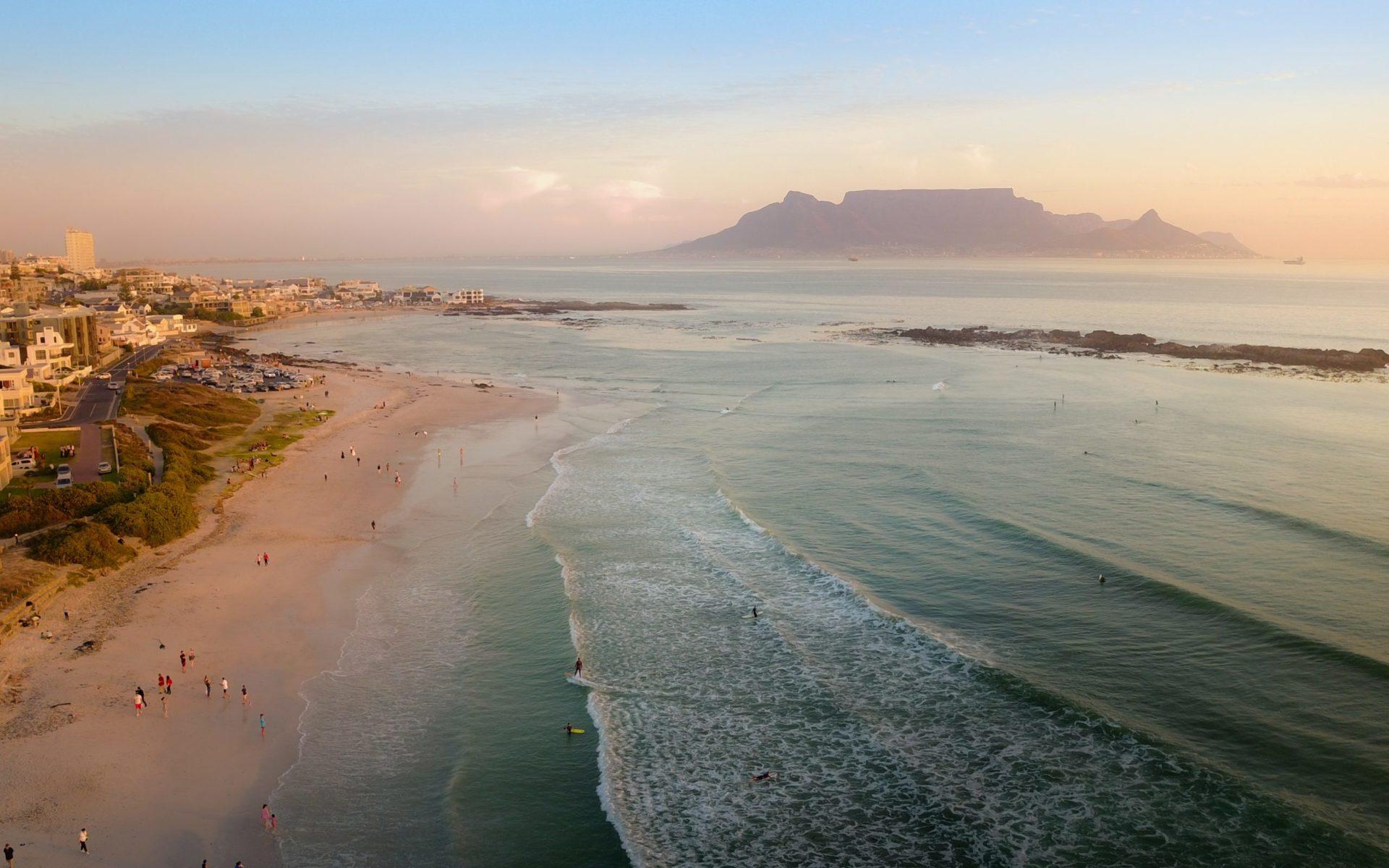 Wassertemperatur Südafrika: Blick aus der Luft vom Strand Big Bay Beach nach Süden auf Kapstadt und den Tafelberg bei Sonnenuntergang