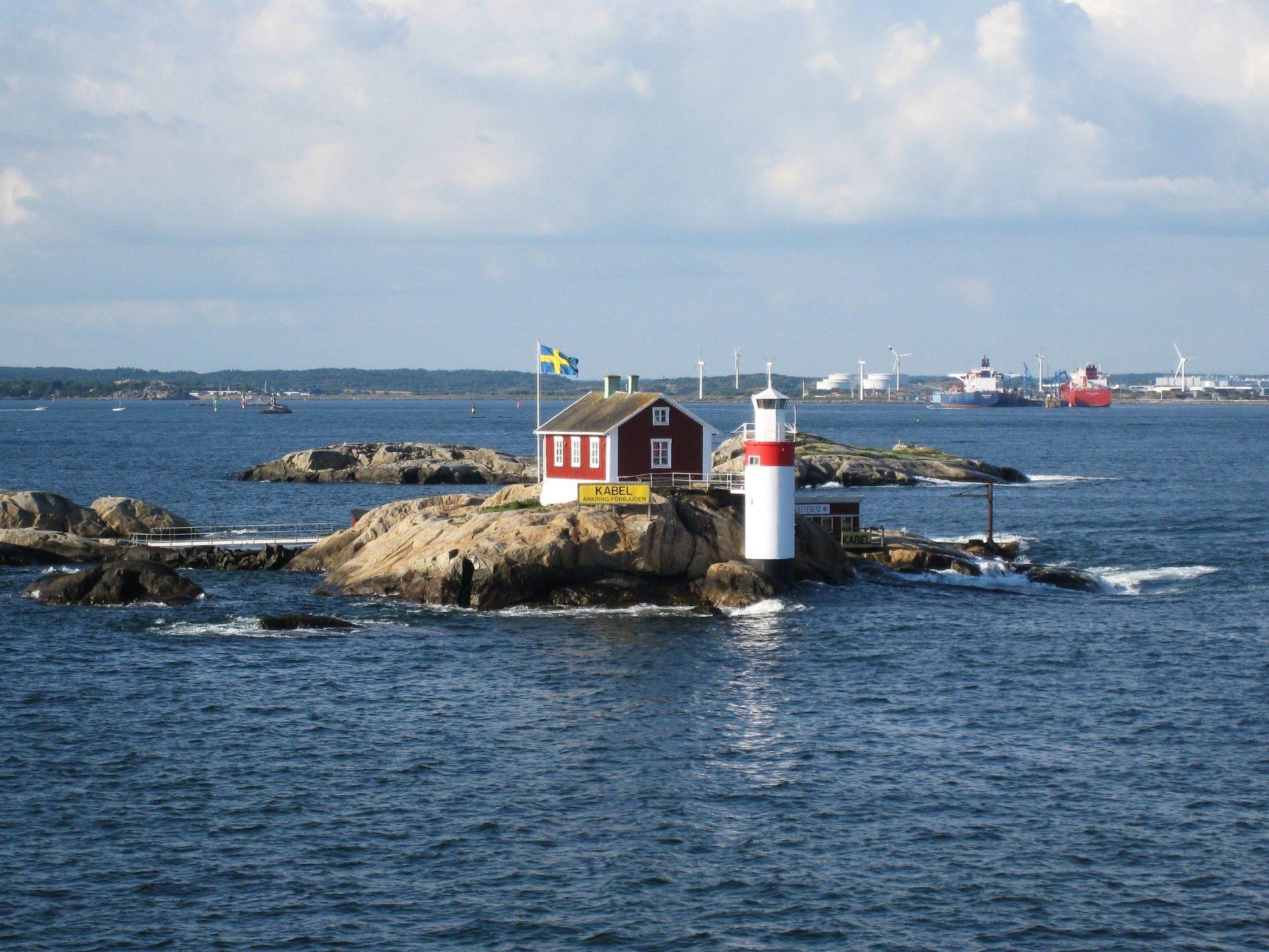 Wassertemperatur Schweden: Insel Gäveskär im Göteborger Schärengarten mit Schwedischer Flagge und mit Falunrot gestrichenem Leuchtturm und Haus