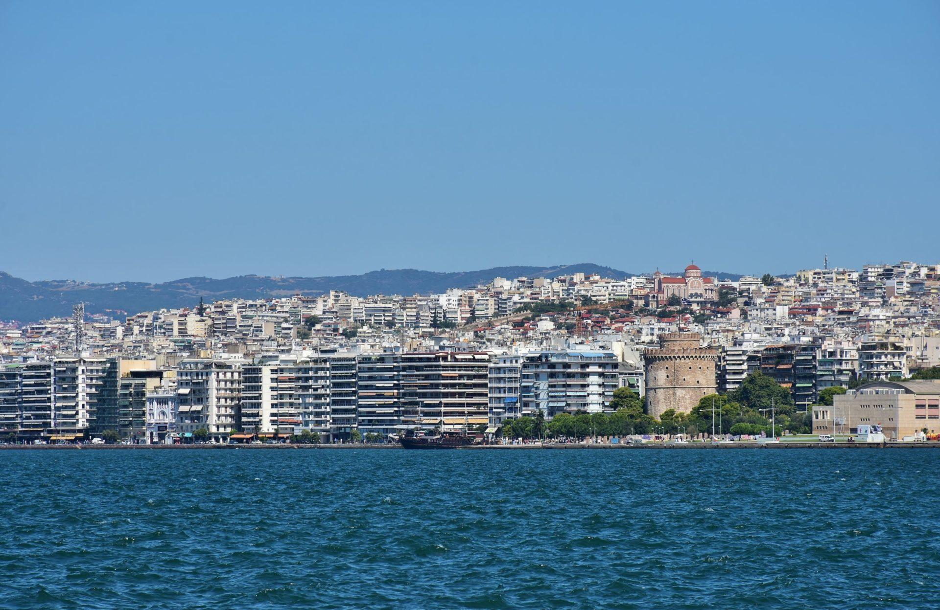 Wassertemperatur Thessaloniki: Blick über den Thermaischen Golf auf das Ufer von Thessaloniki mit dem von Bäumen umgebenen Weißen Turm