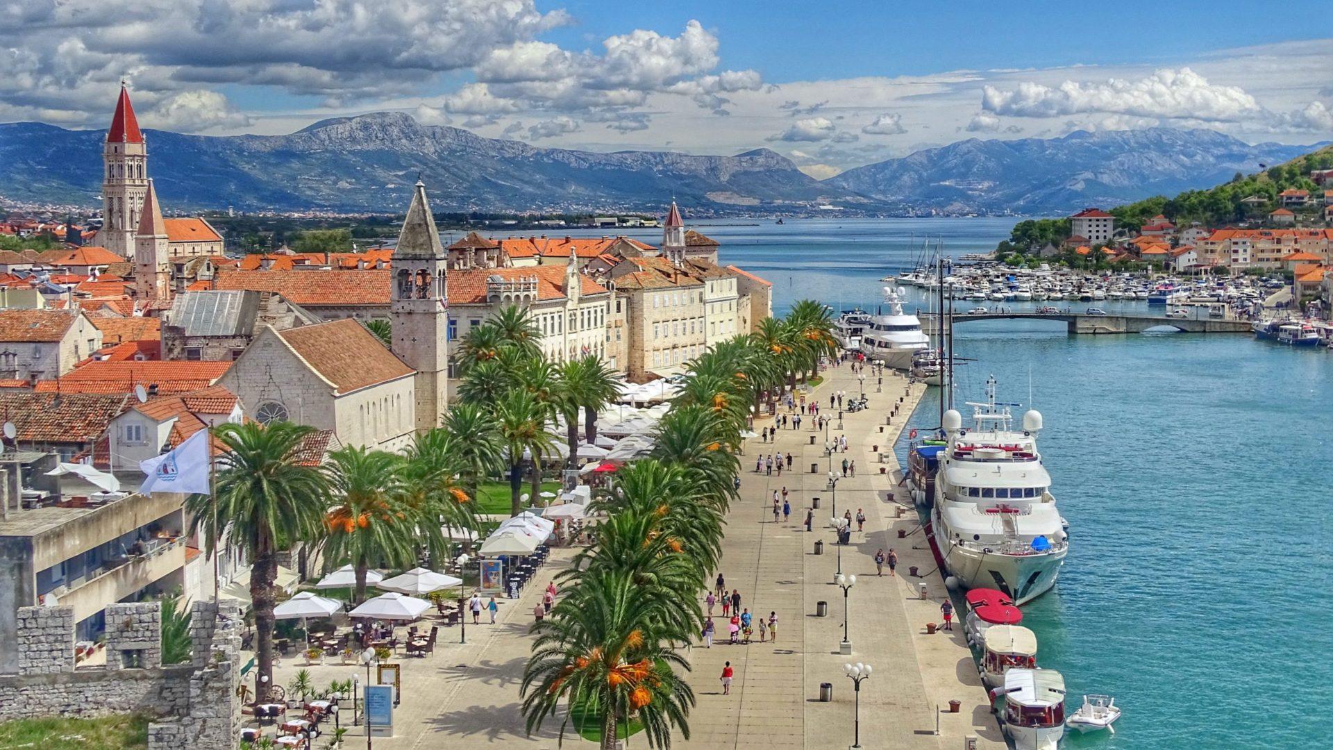 Wassertemperatur Trogir: Uferpromenade und Altstadt von Trogir, ganz links die Laurentius-Kathedrale, rechts die Insel Čiovo